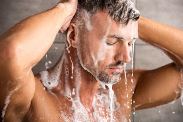 selective focus of adult man with closed eyes washing foam in shower