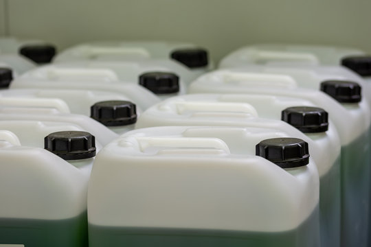 Several chemitry canisters in rows with green liquid