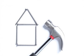 real estate concept: shape of an house made with nails and an hammer isolated on white background with copy space for your text
