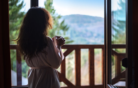 Woman in the morning holding a cup of tea or coffee and looking at the mountains standing near the window .