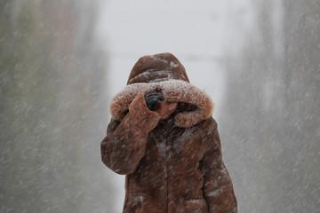 A woman walks along a boulevard amid a snow flurry in central Kiev