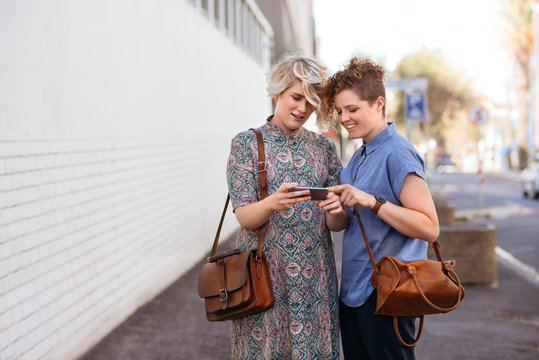 Smiling lesbian couple standing outside looking at cellphone photos