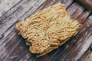 Set of dry raw eggs noodles on wooden food stand. Instant noodles ready to cook.