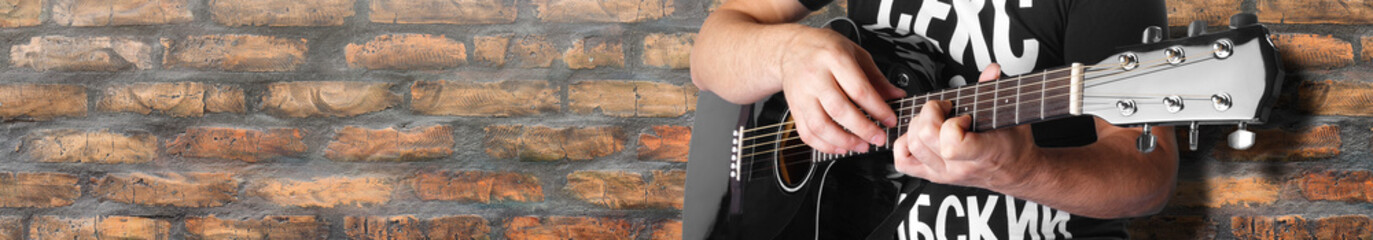 Music - black electric acoustic guitar old brick wall