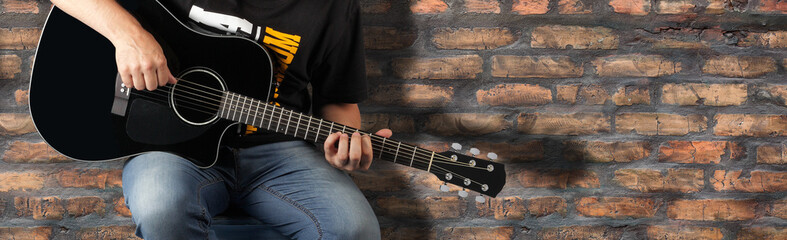 Music - Fragment Man play a black acoustic guitar old brick wall background