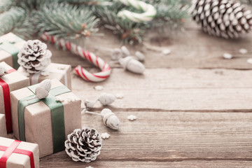 Christmas green branch and gifts on  wooden background