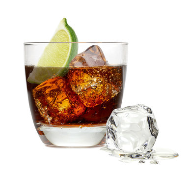Cuba libre drink or tequila cocktail with ice cubes and lime wedge in collins or rocks glass isolated on white background