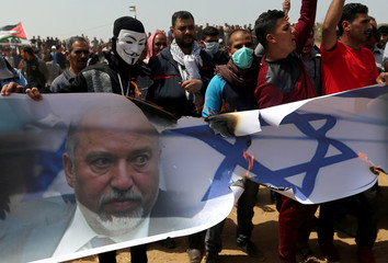 Palestinian demonstrators burn a banner showing a representation of an Israeli flag and a picture of Israeli Defence Minister Avigdor Lieberman during a protest in the southern Gaza Strip