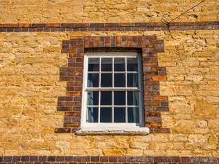 sunny day view of old white window on old brick wall in england