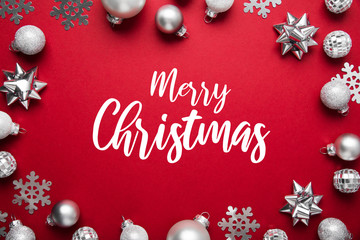 Red Merry Christmas and Happy Holidays greeting card, frame, banner. New Year. Winter holidays. Silver ornaments.