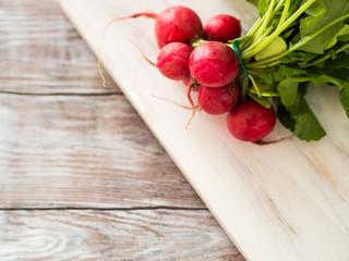Fresh radish on wooden board for salad. Organic food grocery shopping