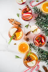 Traditional winter drinks, white and red mulled wine cocktail,  with white and red wine, spices, apple, orange. On a light blue table,