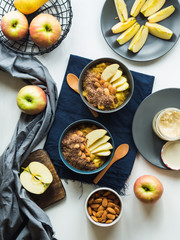Cozy morning concept with turmeric amaranth porridge served with apples, flax seeds and almonds. Healthy plant based vegan breakfast. Flat lay