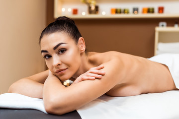 beautiful young woman lying on massage table and looking at camera in spa