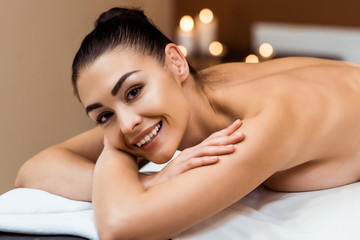 beautiful young woman lying on massage table and smiling at camera in spa