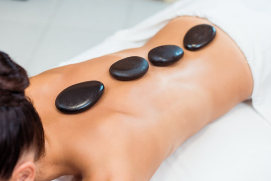 cropped shot of young woman having hot stone massage