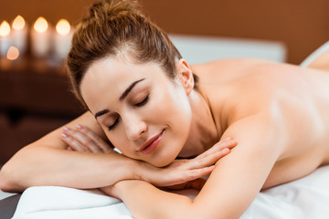 beautiful smiling young woman with closed eyes lying on massage table