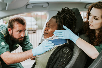 Paramedic placing a cervical collar to an injured woman from car accident