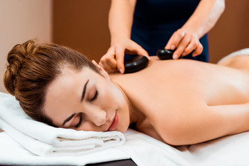beautiful young woman with closed eyes enjoying hot stone massage