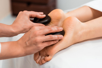 close-up partial view of woman having hot stone massage in spa salon