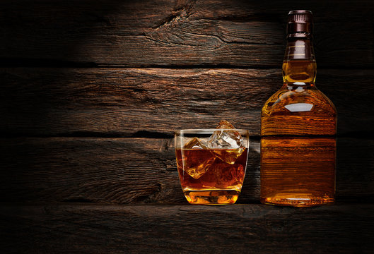 Bottle and glass of whiskey on wooden table or desk background