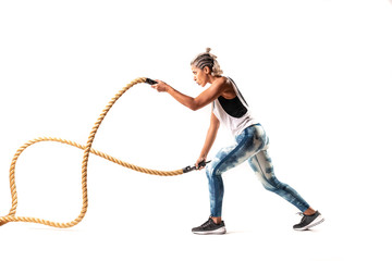 Beautiful female Middle Eastern fitness athlete  with  modern funky hairstyle and wearing sports clothing exercising with battle ropes in studio with white background