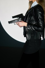 beautiful sexy girl holding gun . projector light background