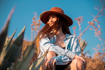 Smiling young woman wearing a hat sitting at an agave in the countyside
