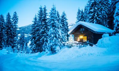 Austria, Altenmarkt-Zauchensee, sledges, snowman and Christmas tree at illuminated wooden house in snow at dusk