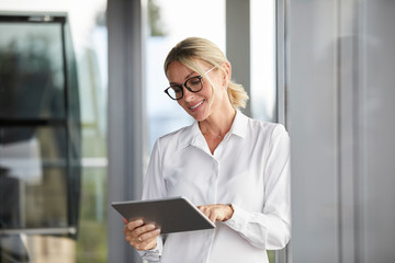 Businesswoman leaning on window, using digital tablet