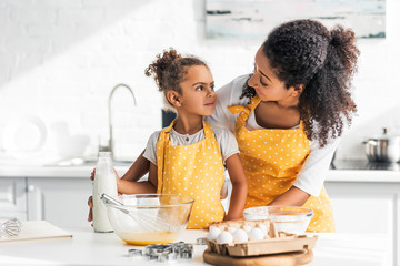 african american mother and daughter looking at each other during dough preparation in kitchen
