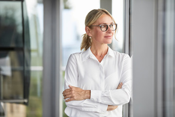 Businesswoman in office leaning against window, with arms crossed
