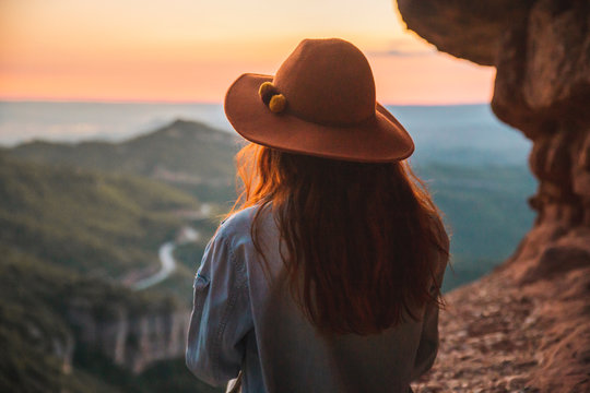 Rear view of woman in hat looking at view during sunset
