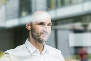 Portrait of smiling businessman looking out of window
