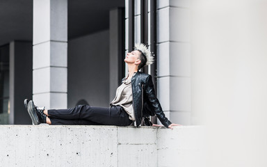 Punk woman sitting on a wall with closed eyes