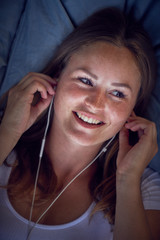 Young woman lying on cushion, listening music with earphones