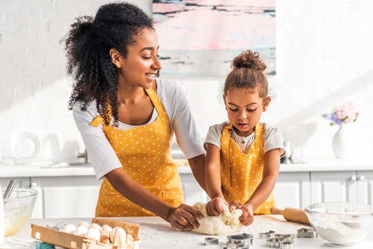 attractive african american mother and adorable daughter kneading dough in kitchen