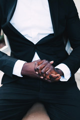 black man in a business suit sitting in a chair, wedding concept. groom black leather. white shirt black suit
