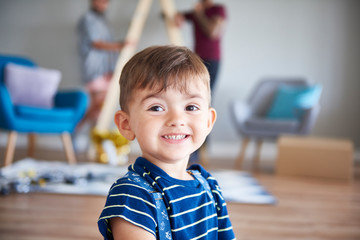 Portrait of smiling boy at home with parents in background