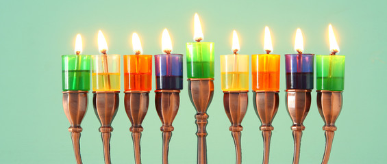 image of jewish holiday Hanukkah background with menorah (traditional candelabra) and colorful oil candles.
