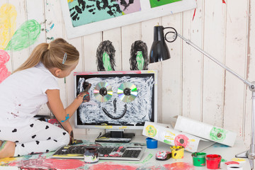 Girl painting rabbit ears on PC in office