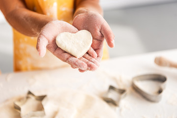 cropped image of african american kid holding heart shaped unbaked cookie in hands in kitchen