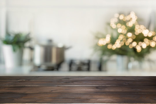 Empty wooden tabletop for display products and blurred kitchen with Christmas tree as background.