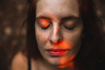 Portrait of young woman with freckles closing her eyes