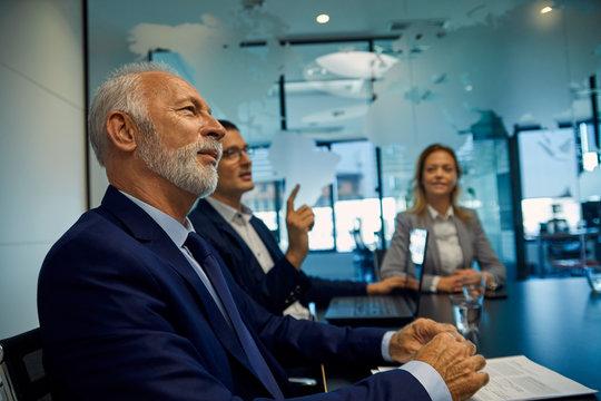 Portrait of senior businessman listening in a meeting