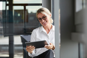 Serene businesswoman sitting on ground in office, using digital tablet