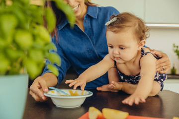Mother with baby daughter eating fruit pulp in kitchen
