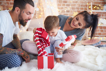 Boy opening Christmas present with his parents in bed