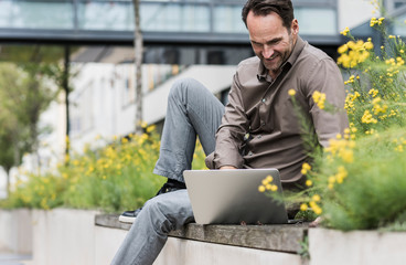 Smiling man sitting on a wall using laptop