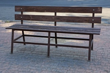 one brown wooden bench stands on a gray sidewalk outside